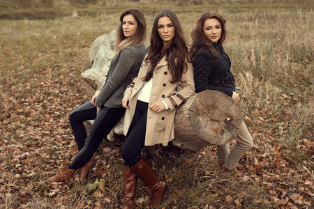 Fashion women posing in autumn scenery photo