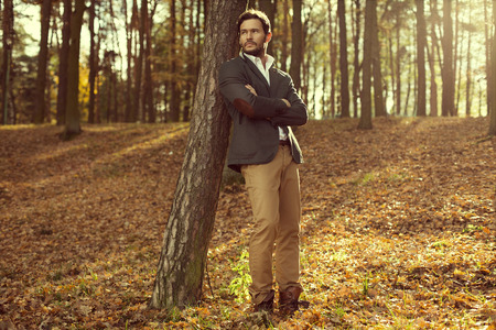 Handsome man in the park. Autumn scenery
