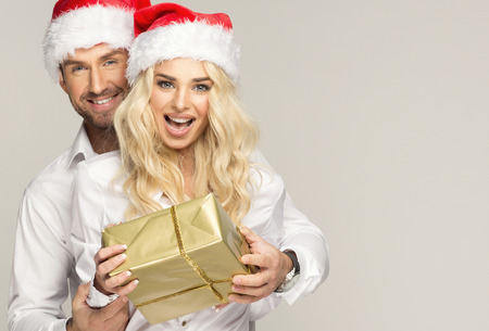 Beautiful smiling couple in santa claus hats with presents photo