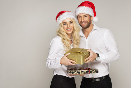Beautiful couple with presents wearing santa claus hat photo