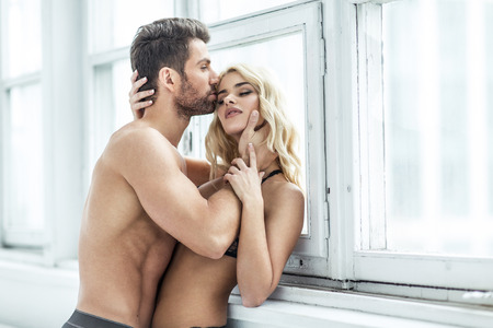 nude wife: Handsome man kissing blond beauty Stock Photo