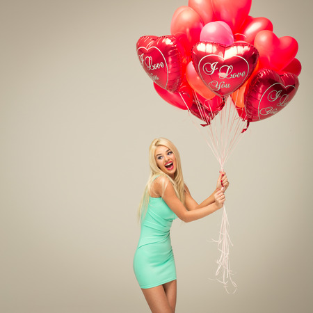young cheerful blond woman with red balloons photo