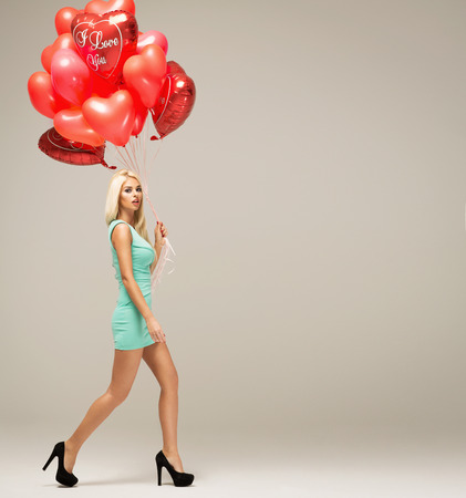 Attractive young blond woman model with balloons in motion isolated on grey background photo