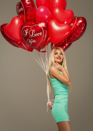 red balloon: Blond woman model with red balloons heart