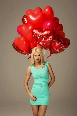 Blond woman model with red balloons heart photo