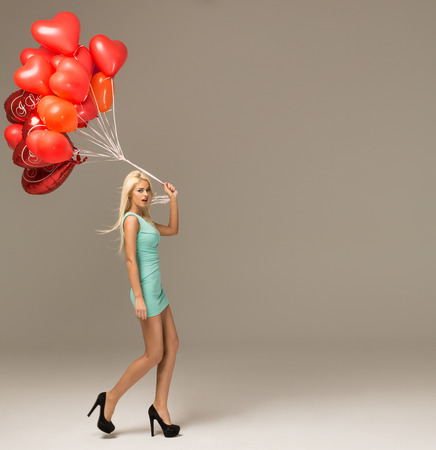 Beautiful blond woman in motion with red balloons photo