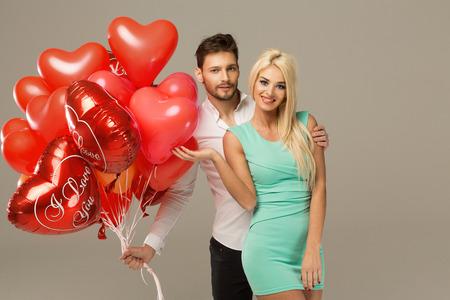 parejas romanticas: Feliz pareja amorosa en fondo gris con globos de corazón