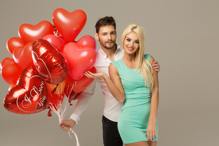 valentine married: Happy loving couple on grey background with heart balloons