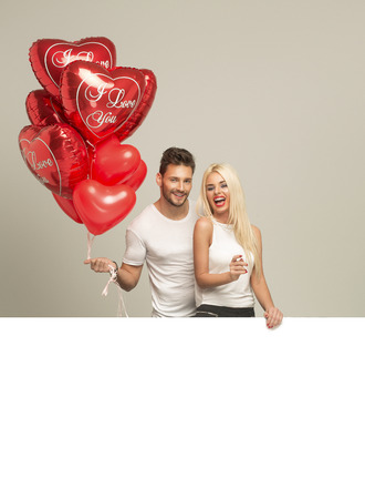 man woman hugging: Young smiling couple with red balloons heart and white empty space