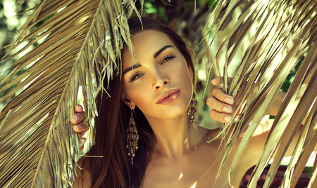 natural make up: Beautiful woman between palm leaves