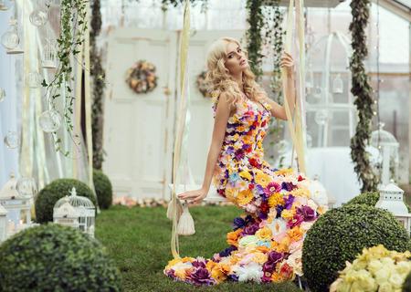 modelos posando: Señora de la manera en un paisaje de primavera con un vestido de flores