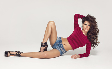 culo di donna: Moda Giovane donna sexy sdraiata sul pavimento mostrando le gambe e guardando la camera. Archivio Fotografico