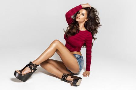 piernas con tacones: Seductora mujer atractiva que se sienta en el suelo y mirando a la cámara