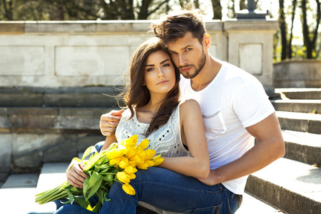 Portrait of unusual couple with yellow tulips sitting and resting