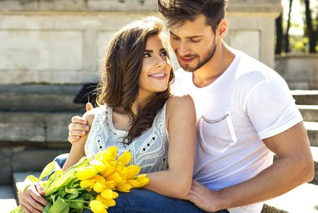 Aantrekkelijk paar met gele tulpen zitten en samen te rusten in de zomer
