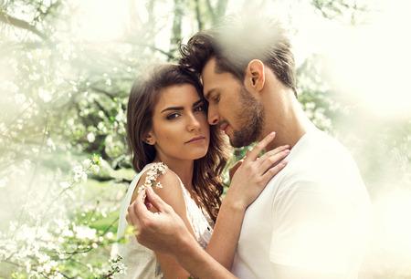 pareja abrazada: Retrato de la joven pareja en contacto entre sí en el jardín Foto de archivo