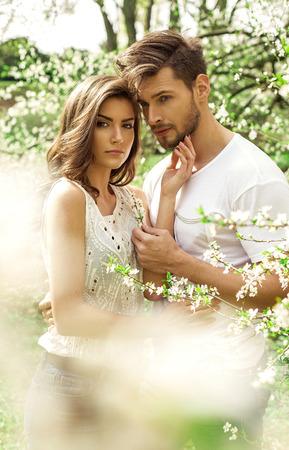 dia soleado: Retrato de una hermosa pareja en el jardín en flor Foto de archivo