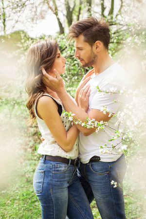 Cute couple touching each other in the blooming garden