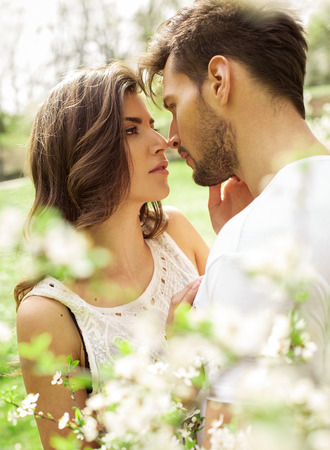 man woman hugging: Portrait of kissing couple in the blooming garden Stock Photo