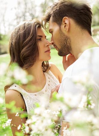 Portrait of kissing couple in the blooming garden Foto de archivo