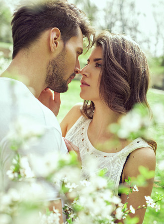 summer beauty: Portrait of kissing couple in the garden