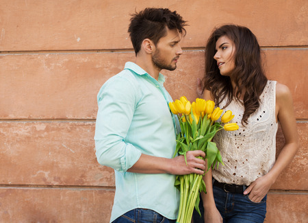 kiss couple: Handsome man giving a bouquet of tulips young woman