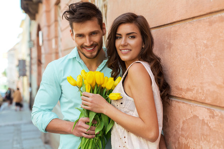 Portrait of beautiful happy couple with yellow tulips