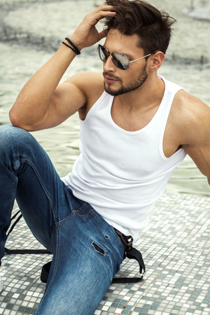 Sexy man in aviator sunglasses touching his hair