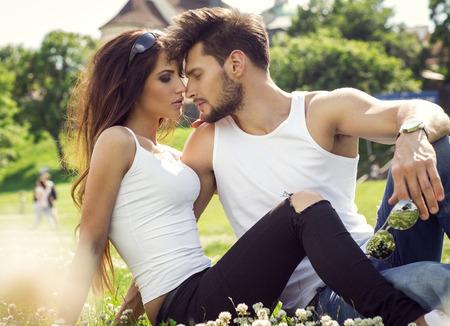 매력적인 젊은 부부는 풀밭에 휴식과 서로 만지고 스톡 콘텐츠