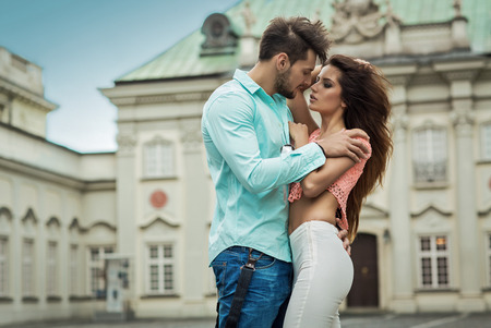 sensual: Sexy young kissing couple in love. Outdoor shot on blurred background