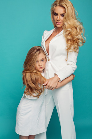 Fashion photo of beautiful mother and daughter in white clothes isolated on turquoise background Stock Photo