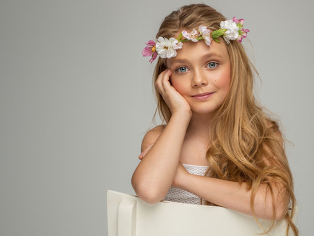 pretty dress: Fashion portrait of beautiful little girl with wreath Stock Photo