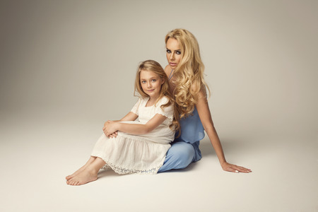 beautiful background: Beautiful mother and daughter posing in studio