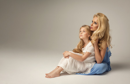 female child: Mother and daughter sitting on the studio background and looking up Stock Photo