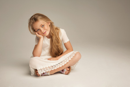 child charming: Smiling little girl sitting on studio background Stock Photo