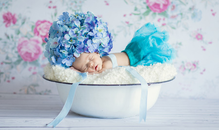innocent: Newborn baby girl with flowers hat asleep Stock Photo