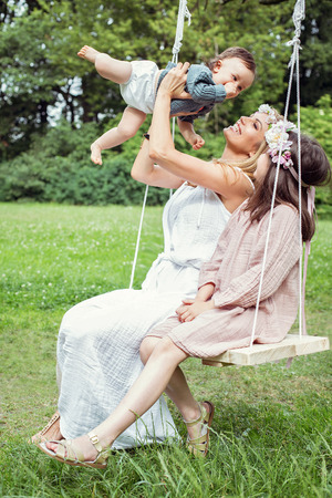 two children: Mother and children sitting on a swing