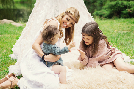 teepee: Mother and children are sitting in a tent teepee and having fun with a nature