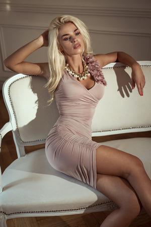 blonde woman: Sexy blond woman sitting on stylish sofa