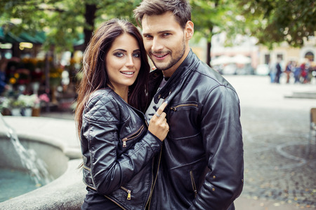leather background: Portrait of attractive couple in leather jacket. Autumn photo