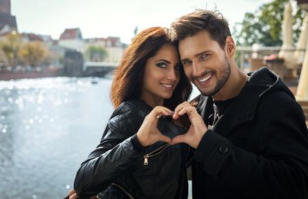 Sexy lachende paar kijken door en het maken van de vorm van het hart door hun handen