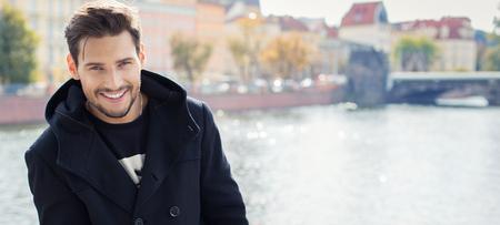 uomini belli: Foto Paronamic con bel uomo sorridente in cappotto