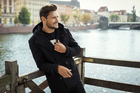 mode: Foto des stattlichen lächelnden Mannes im schwarzen Mantel in Herbstlandschaft