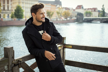 mode: Foto van de knappe lachende man in zwarte jas in de herfst landschap