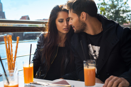 Loving couple drinking orange juice and kissing each other outdoor