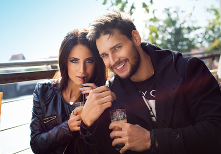 Happy couple drinking orange juice in autumn time Stock Photo