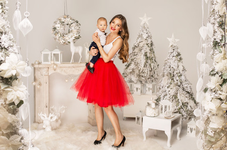 Young mother with her cute child posing in christmas scenery