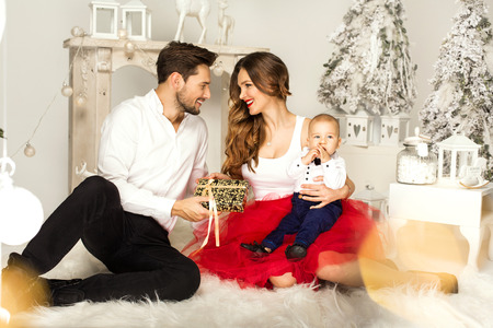 baby open present: Happy Familly with Christmas and New Year Gift at Home Stock Photo