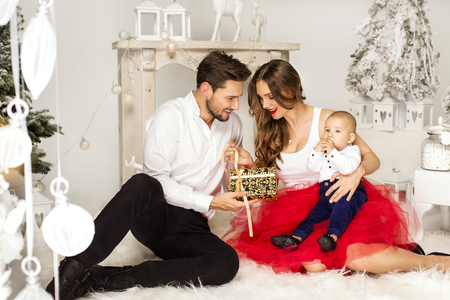 baby open present: Father giving a christmas present to his wife. Happy familly in Christmass Time