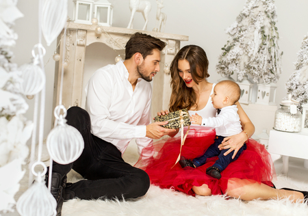 baby open present: Happy Familly opening a Christmas Present. Happy familly in Christmass Time Stock Photo